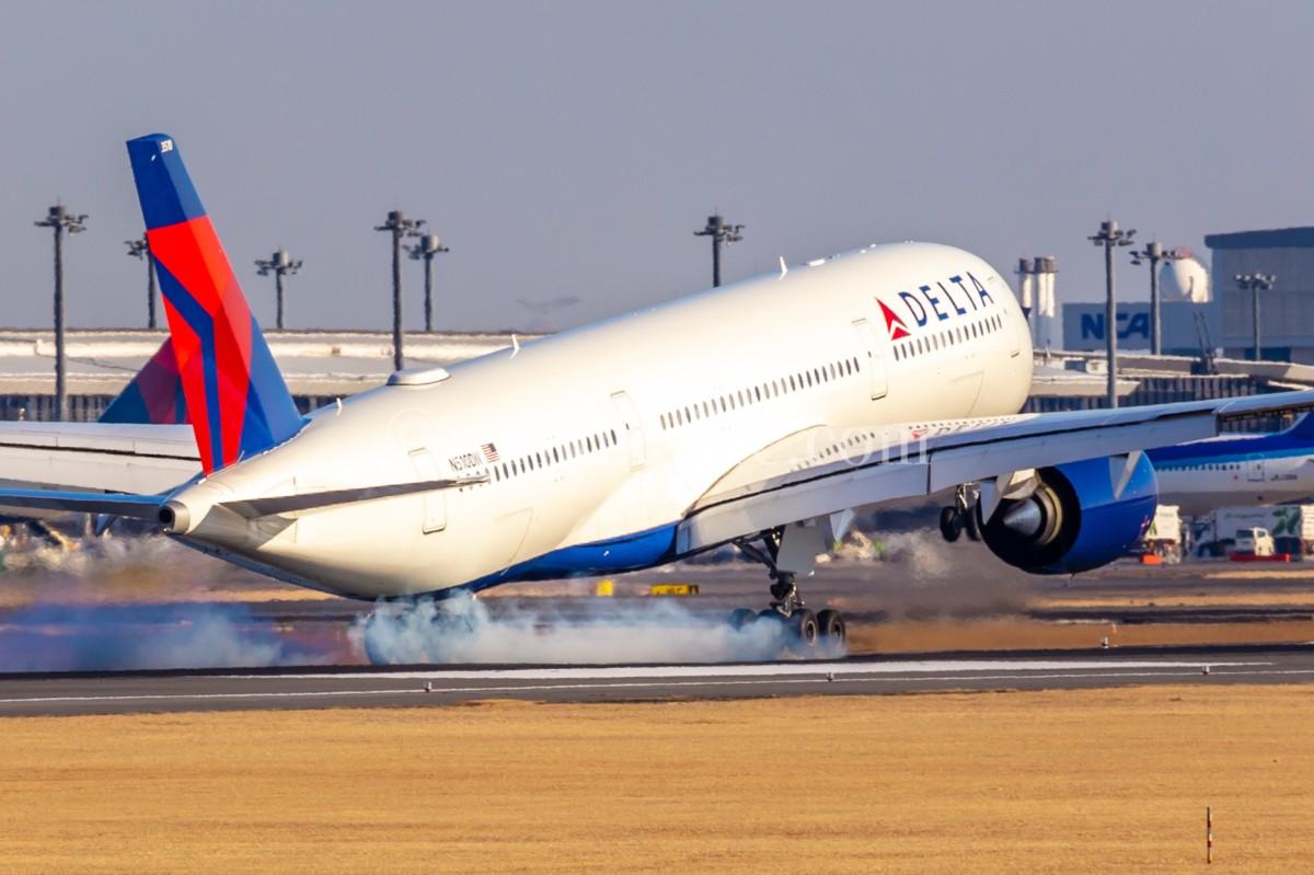 成田空港A滑走路に着陸しギアからスモークを上げる飛行機