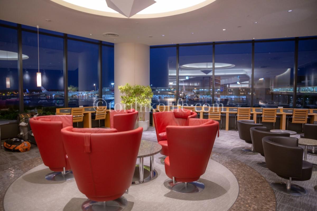 大きな窓と赤いソファーが特徴的なアメリカン航空ラウンジ内の様子